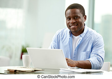Successful man - Image of young African businessman looking...