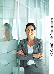 Businesswoman - A beautiful businesswoman by wall looking at...