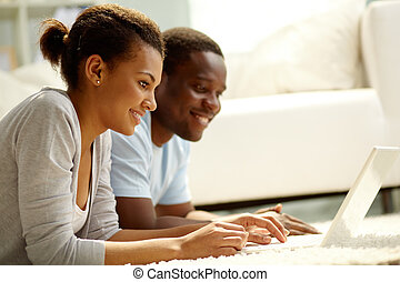 Web work - Image of young African couple networking at home