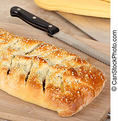 Baked Stromboli - Baked stromboli on a cutting board to be...