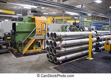 Machine shop interior with manufactured steel tubes in...