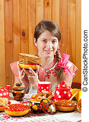 Girl in traditional  clothes with pancake