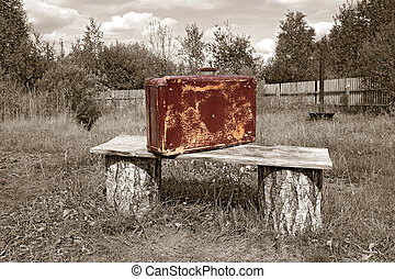 old valise near wooden bench, sepia