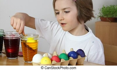 Little girl coloring Easter eggs