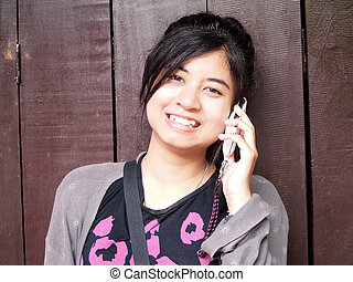 beautiful girl with mobile phone on wood background.