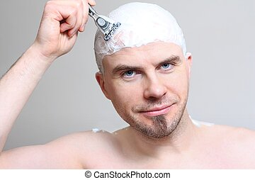Shaving head - Young man with razor shaving head