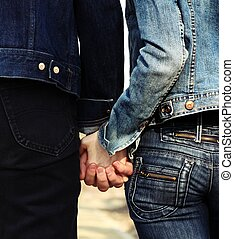 Holding hands - Pair of young people dressed casually...