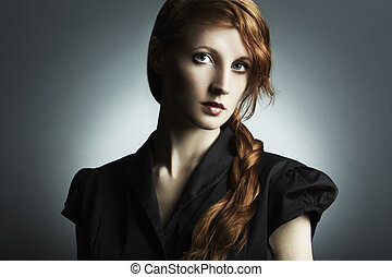 Fashion photo of a beautiful young red-haired woman....