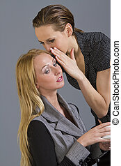 two girls gossiping - Woman telling a secret to another -...