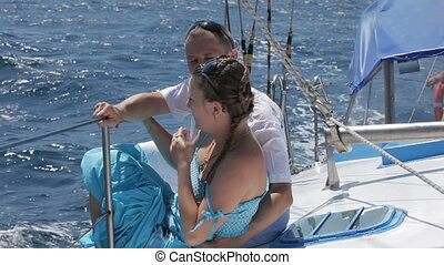 Young couple is traveling on yacht - Young couple is...