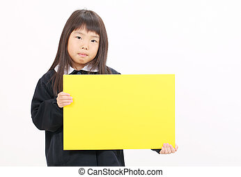 Little asian schoolgirl holding a blank board