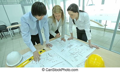 Discussing blueprints - Group of three architects discussing...