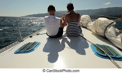 Young couple is on bow of the yacht - Happy boy and girl are...