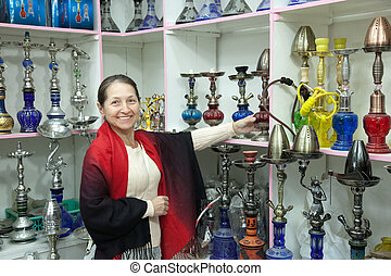 woman chooses sheesha in shop - Mature woman chooses sheesha...