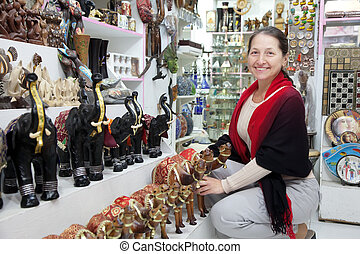 woman chooses souvenirs at shop - woman chooses souvenirs at...