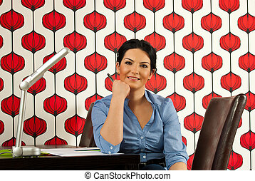 Smiling business woman sitting at desk in her modern office