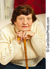Portrait of elderly woman resting her face on hands with...
