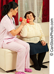 Nurse helping senior woman and explaining how to make...