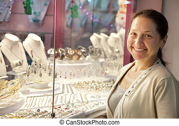 Happy mature woman looking jewelry counter