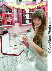 girl chooses ring at  shop