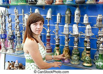 woman chooses  sheesha in  shop