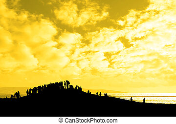 silhouette of a crowd on a hill