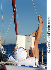 Young woman reading and sunbathing on sail boat - Young...