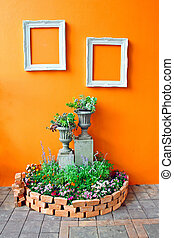 decoration of small garden with frames on orange wall