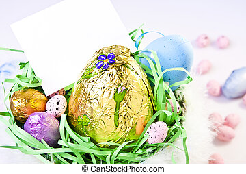 An Easter basket full of chocolate eggs, with a blank, customizable card.