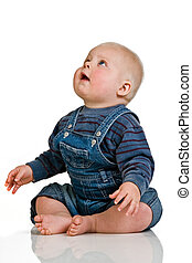 Baby boy looking up - Baby boy in blue dungarees and a...