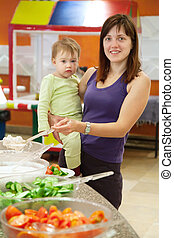 Woman with chid  chooses  snack  in buffet