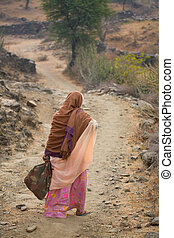 Old woman on track - Old Indian woman walking down a country...