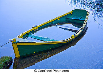 Sunken row boat in blue water - A sunken row boat in still...