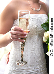 The hand of the bride holds a beautiful glass with champagne