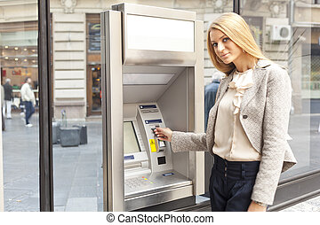 Woman using Bank ATM machine - Young Woman using Bank ATM...