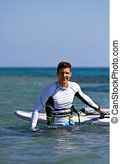 Happy windsurfer coming out of water