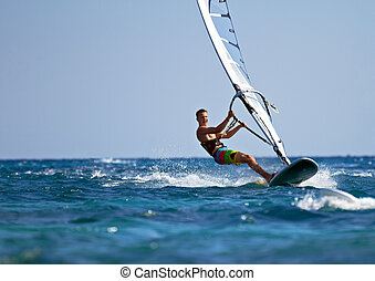 Fast approaching windsurfer - Young man surfing the wind on...
