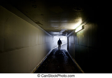 Light at End of Tunnel - Silhouette of a man walking in a...