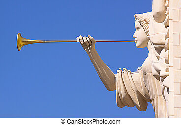 A trumpeting golden music angel statue detail over blue sky....