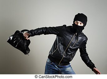Portrait of running male burglar with a handbag