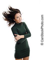 Model in green dress flinging long hair into air. Isolated on white.