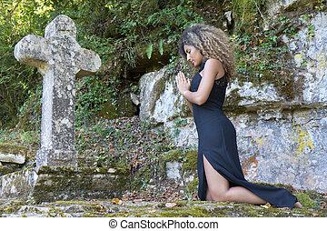 Woman  kneeling near a cross