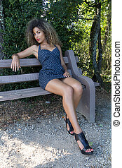 Sexy woman sitting on a bench She is wearing a short spotted...