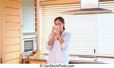 Woman lifting up and drinks a cup of coffee