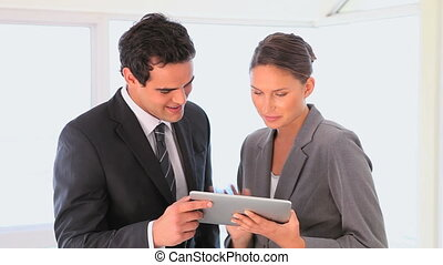 Business man and woman looking at a tablet while they smile...