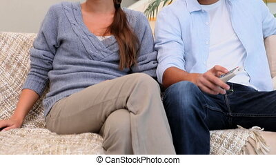 Man and woman sitting on the couch watching TV