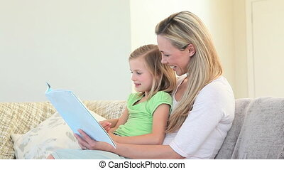 A mother and daughter sit on the couch looking at a picture...