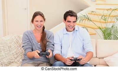 Man and woman sitting on the couch playing console games...