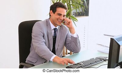 Business man sits in front of his computer typing while he...