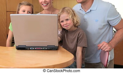 Family sitting in front of a laptop as they all wave to the...